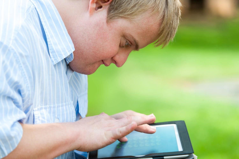 Bild zeigt: Geistig behinderter Mann mit Tablet