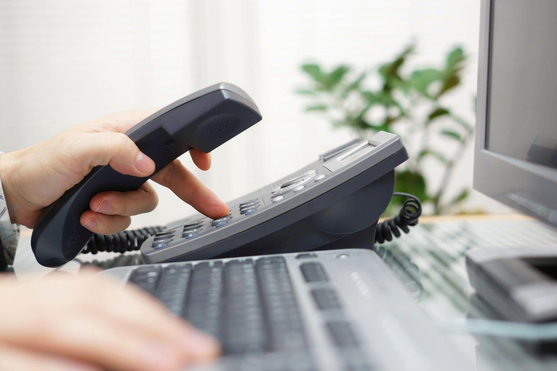 Bild zeigt: Eine Hand am Telefon und eine auf der Computertastatur in einem Büro
