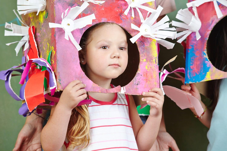Bild zeigt: Mädchen trägt eine gebastelte Kopfbedeckung