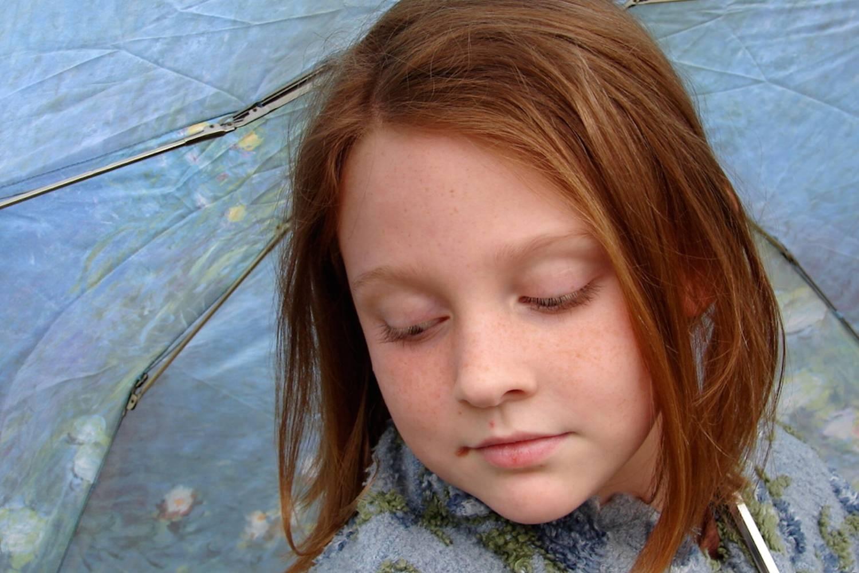 Bild zeigt: Portrait eines Mädchens unter einem Regenschirm