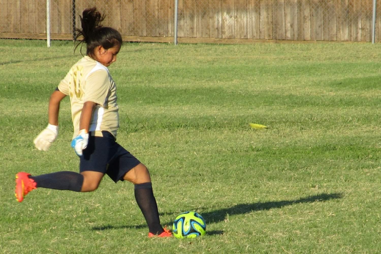 Bild zeigt: Junges Mädchen im Trikot tritt nach einem Fußball