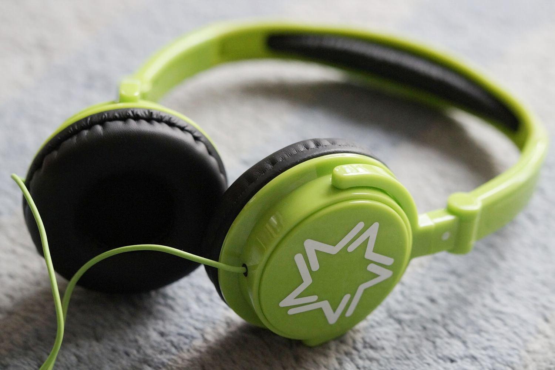 Bild zeigt: Ein grüner Kopfhörer liegt auf einem Tisch