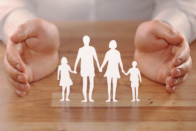 Bild zeigt: Silhouette einer Familie, ausgeschnitten aus weißem Papier, schützend umgeben von beiden Händen