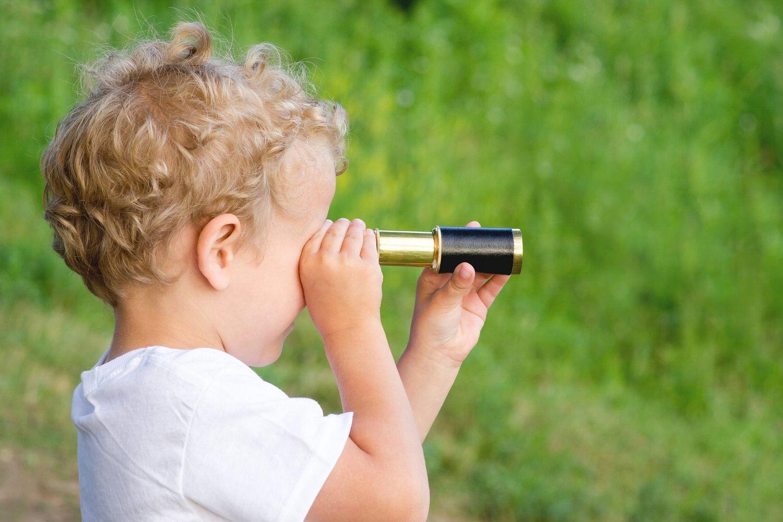 Bild zeigt: Kleinkind mit kleinem Fernrohr vor den Augen