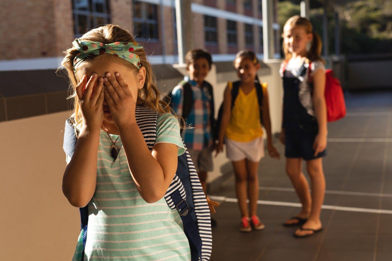 Bild zeigt: Junge Schülerin weint und Kinder dahinter lachen