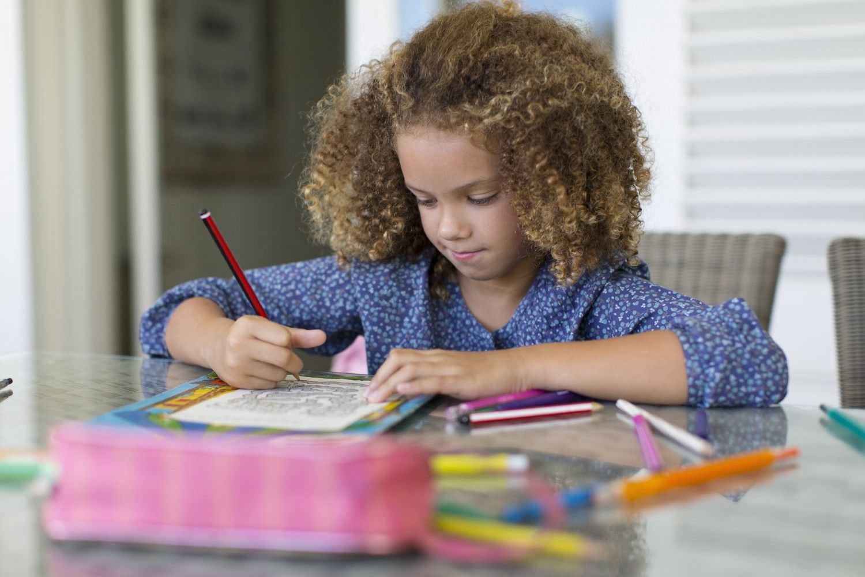 Bild zeigt: Mädchen mit Lockenkopf sitzt am Tisch und macht Hausaufgaben