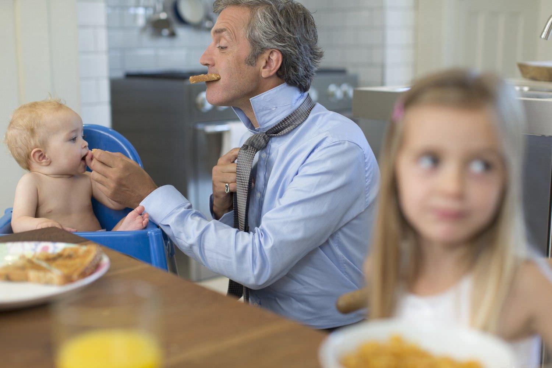 Bild zeigt: Vater mit zwei Kindern beim Frühstück in Eile