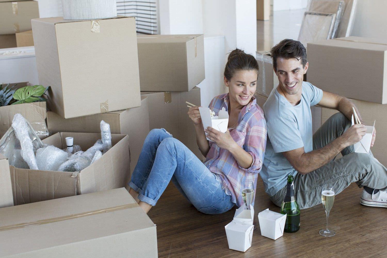 Bild zeigt: Junges Paar sitzt zwischen Umzugskisten mit Essen in der Hand