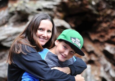 Bild zeigt: Mutter umarmt ihren Sohn von hinten