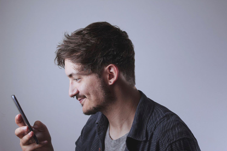 Bild zeigt: Junger Mann mit Bart sieht auf sein Smartphone