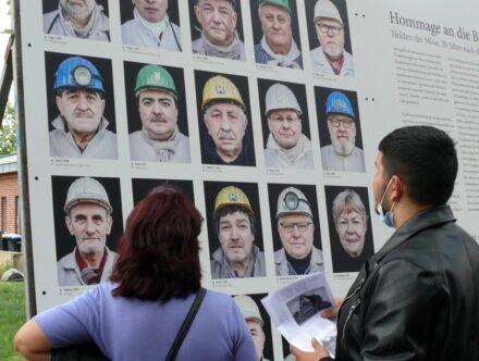 Bild zeigt: Zwei Menschen sehen auf die ausgestellte Tafel mit Bergleuten