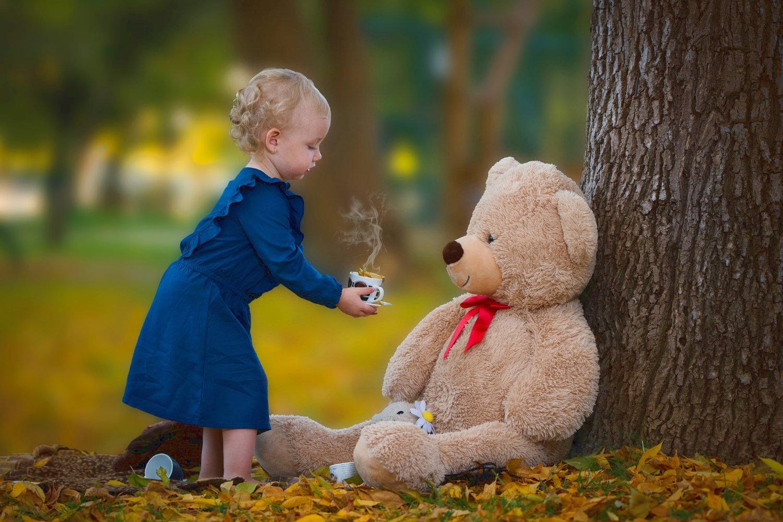 Bild zeigt: Kleines Mädchen reicht einem großen Teddybär eine Tasse Tee
