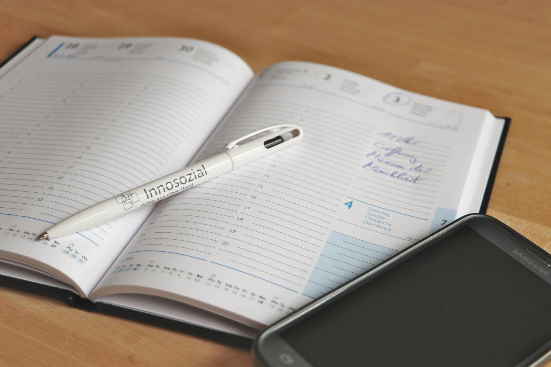 Bild zeigt: Offener Buchkalender mit Kugelschreiber und Handy