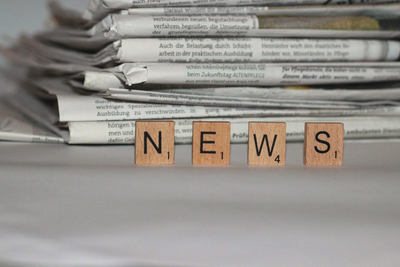 Bild zeigt: Großaufnahme der Scrabble-Buchstaben N E W S vor einem Stapel Tageszeitungen