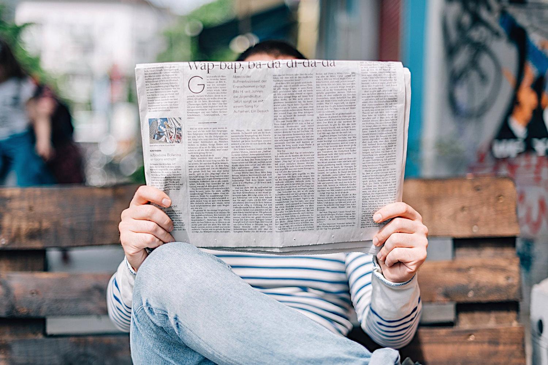 Bild zeigt: Ein Mann liest Zeitung und verbirgt dahinter sein Gesicht