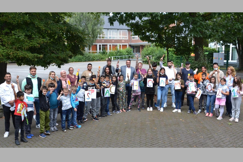 Bild zeigt: Der Bürgermeister umringt von Kindern und Betreuer*innen des Sprachcamps
