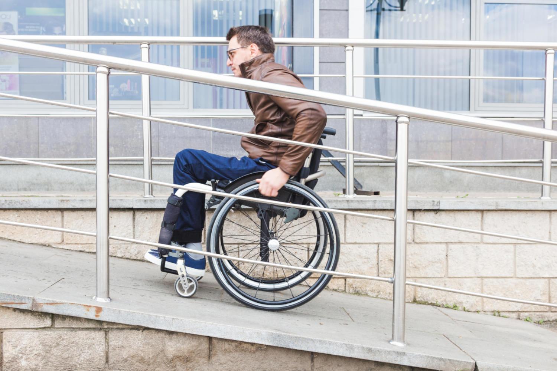 Bild zeigt: Ein Mann mit Behinderung fährt mit seinem Rollstuhl eine Rampe hoch