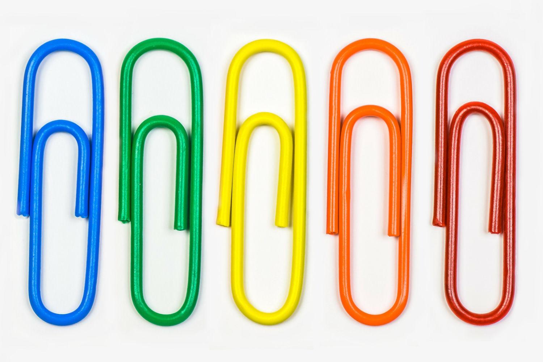 Bild zeigt: Großaufnahme von fünf Büroklammern in den Farben Blau, Grün, Gelb, Orange und Rot